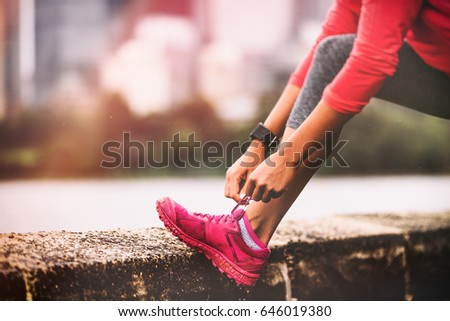 Runner woman getting ready to run tying running shoes laces. Healthy lifestyle jogging motivation closeup of feet or footwear.