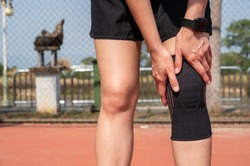 Runner woman holding her knee while she having suffering from knee pain and she wearing knee braces for supports to be worn when you have pain in your knee.
