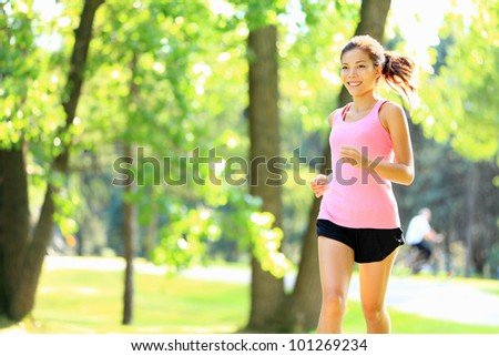 Runner - woman running in city park on sunny summer day with with sunshine in green trees. Asian / Caucasian fitness sports model during outdoor workout.