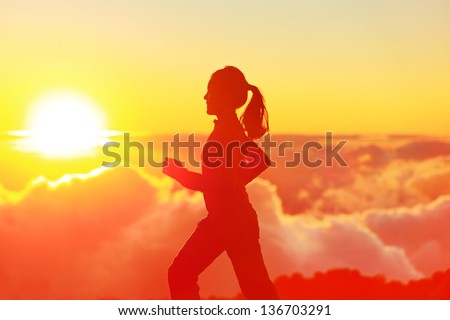 Runner woman running in sunshine sunset Fitness athlete training trail running marathon in mountains above the clouds in beautiful mountain landscape Female in jogging in silhouette