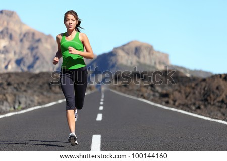 Runner woman running on mountain road in beautiful nature. Asian female sport fitness model jogging training for marathon during outdoor workout.