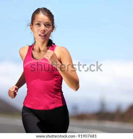 runner - woman running outdoors training for marathon run. Beautiful fit asian fitness model in her 20s.