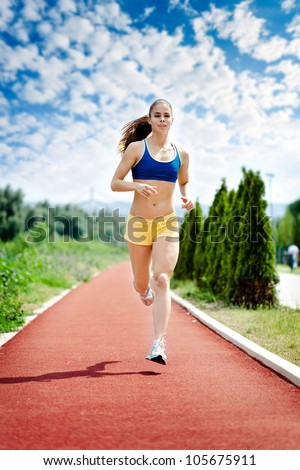 runner - woman running outdoors training for marathon run. Beautiful fitness model in her 20s.