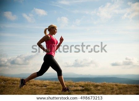 runner - woman runs cros country on a path in early autumn #498673213