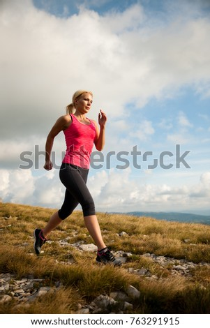 runner - woman runs cros country on a path in early autumn #763291915