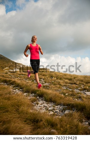 runner - woman runs cros country on a path in early autumn #763319428