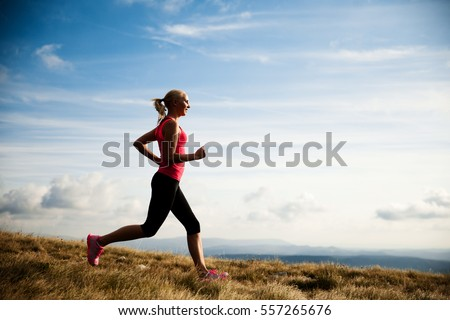 runner - woman runs cross country on a path in early autumn #557265676
