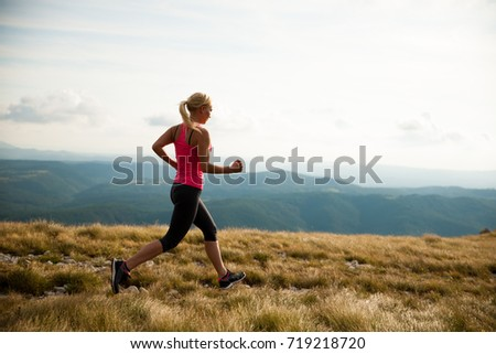 runner - woman runs cross country on a path in early autumn #719218720