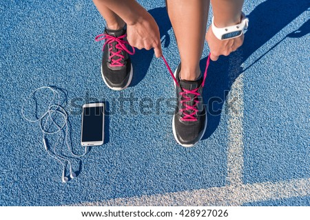 Runner woman tying running shoes laces getting ready for race on run track with smartphone and earphones for music listening on mobile phone. Athlete preparing for cardio training. Feet on ground.