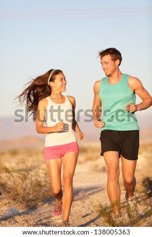 Runners - Active fitness couple running and laughing together outside. Happy runner woman and jogging man working out smiling during cross-country trail run. Asian female model and Caucasian male.