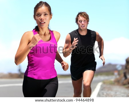 Runners - couple running training for marathon. Sport woman & man jogging on road outside. Athletic female runner and male fitness model running at speed. Young Caucasian man and beautiful Asian woman
