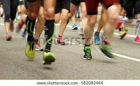 Runners feet on the road in blur motion during a long distance running event #582082444