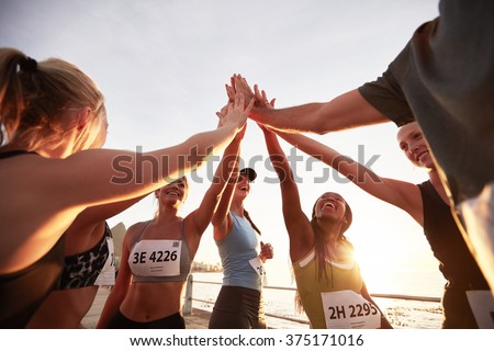 Runners high fiving each other after a good training session. Group of athletes give each other high five after race.