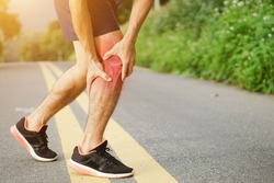 Runners leg pain, man holding sore and over trained painful leg muscle or cramp .Injured over trained person when exercising or running jogging outdoors.