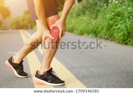 Runners leg pain, man holding sore and over trained painful leg muscle or cramp .Injured over trained person when exercising or running jogging outdoors. Stock photo ©