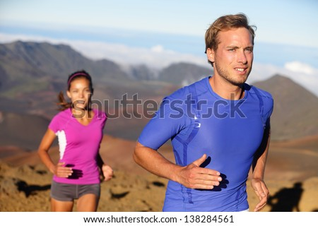 Runners trail running athletes. Young fitness runner couple training trail running cross-country run for marathon. Fit man in compression t-shirt and woman model working out together. Multiracial.