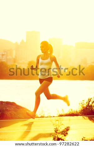 runners - woman running outdoors in sunshine. Young woman jogging in city of Montreal, Quebec, Canada,