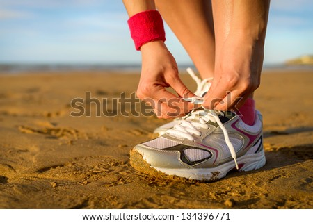 Running and jogging exercising concept. Woman tying laces before training on beach. Unrecognizable caucasian girl wearing sport shoes.