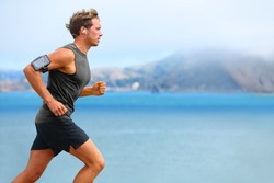Running app on smartphone. Male runner listening to music jogging with armband for smart phone. Fit man fitness model working outdoor by water.