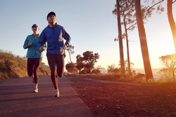 Running at sunrise couple exercising for marathon and workout fitness