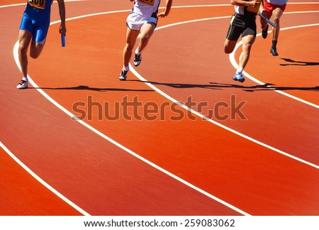 Running athletes at stadium in relay race athletics competition