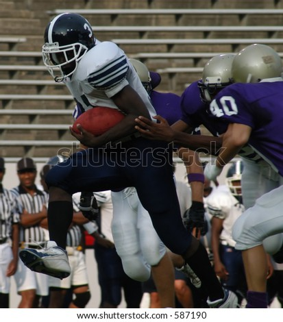 Running back breaking through tacklers at the line of scrimmage