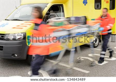 Running blurry paramedics team with stretcher and ambulance car
