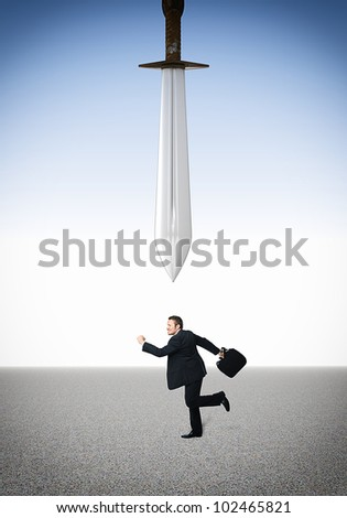 running businessman and damocles sword - stock photo