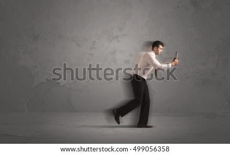 Running businessman in a rush with device in hand on background #499056358