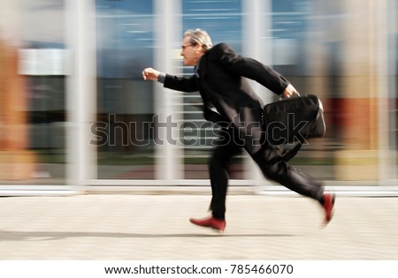 Running Businessman in front of generic modern office buildings with action and motion blur