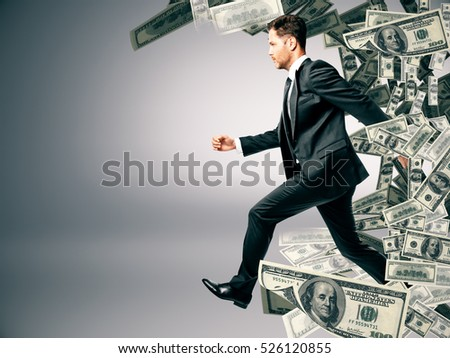 Running businessman with dollar banknote wave ob grey background. Success and wealth concept #526120855