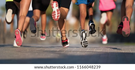 Running children, young athletes run in a kids run race,running on city road detail on legs,running in the light of morning