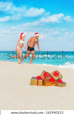 Running couple in santa hats at sea sand beach with christmas packed  golden gifts