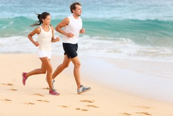 Running couple jogging on beach exercising and jogging training. Sport runners working out on summer beach. Asian woman, Caucasian man.