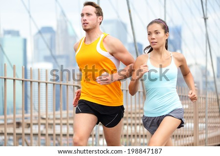 Running couple jogging training for New York marathon. Runners on run outside. Asian woman and Caucasian man runner and fitness sport models jogging on Brooklyn Bridge, New York City, USA.