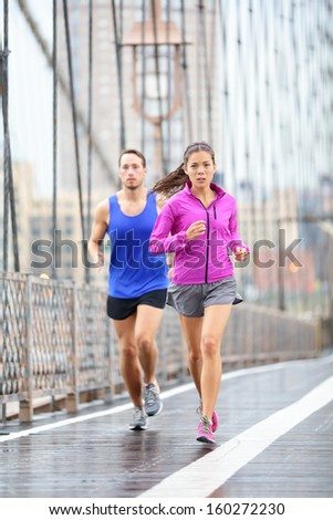 Running couple Runners jogging outside in rain Woman and man runner athletes training outdoor for marathon on Brooklyn Bridge New York City USA Asian female and Caucasian male fitness sport model