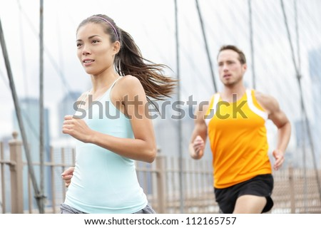 Running couple. Woman and man runner athletes training outside for marathon. Photo from Brooklyn Bridge, New York City, USA. Asian woman and Caucasian man fitness sport models.