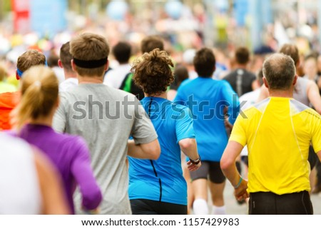 Running crowd at the marathon. Many runners passing the start or finish line. #1157429983
