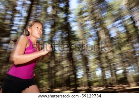 Running, Female runner running fast at great speed in forest. Motion blurred image of beautiful Asian / Caucasian woman athlete sprinting outdoors in tank top.