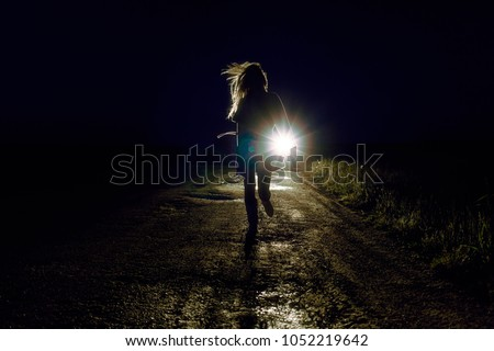 running female silhouette on a night country road running away from pursuers by car in the light of headlights