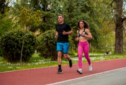Running fitness couple of runners doing sport on road outdoor. Active living man and woman jogging training cardio in summer outdoors nature