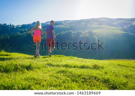 Running fitness couple of runners doing sport on road outdoor. Active living man and woman jogging training cardio in summer outdoors nature.