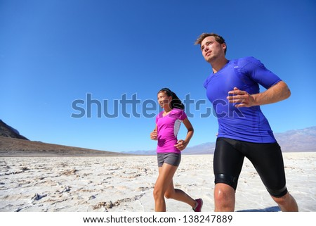 Running fitness sport runners in extreme run training in the desert. Athlete running multiracial running couple. Fit caucasian man sports model and sporty Asian woman exercising outdoors in summer.