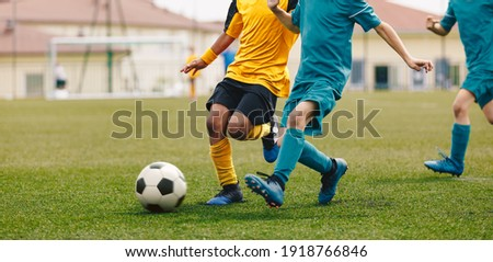 Running Footballers. Children Kicking Soccer School Tournament Match. Multiethnic Children Playing Sports. Young Athletes Compete in Football Game
