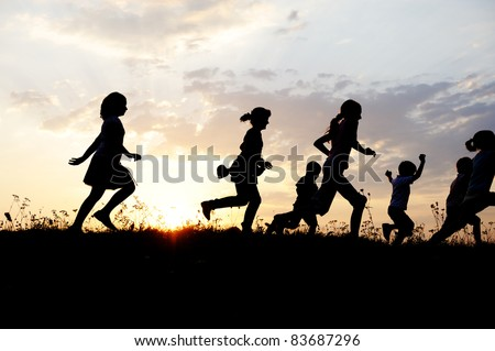 Running group of children running on meadow, sunset, silhouette