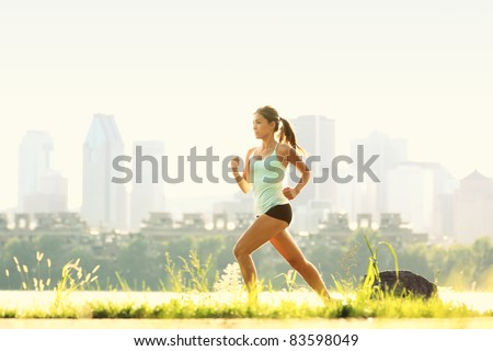 Running in city park. Woman runner outside jogging with Montreal skyline in background