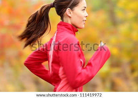 Running in Fall Runner woman jogging in autumn forest Beautiful young fit fitness sport model jogging with slight motion blur Mixed race Caucasian Asian girl.