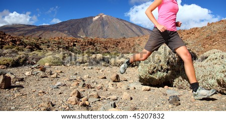 Running in spectacular volcano landscape on Teide, Tenerife. Woman in pink top.