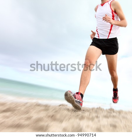Running legs and shoes of runner jogging on beach. Caucasian sport man training for marathon.
