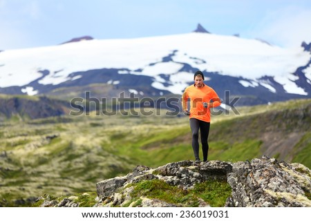 Running man exercising - trail runner athlete. Fit male sport fitness model training and jogging outdoors living healthy lifestyle in beautiful mountain nature, Snaefellsjokull, Snaefellsnes, Iceland.